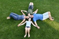 Família, pai, mãe, filho e filha encontrando-se no prado
