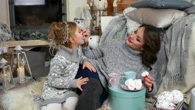 A família pela chaminé que come uma sobremesa com chá, mum alimenta o bolinho de amêndoa da filha, a mãe e o Natal comido criança video estoque