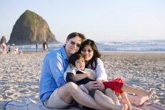 Família pequena com o menino incapacitado que senta-se na praia Imagem de Stock