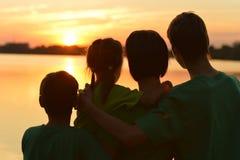 Família perto do rio contra o por do sol Fotografia de Stock Royalty Free
