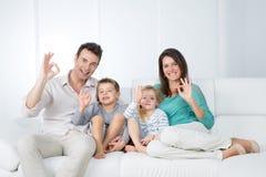 Família positiva que senta-se no sofá Foto de Stock Royalty Free