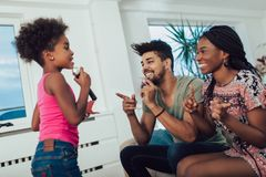 A família preta aprecia cantar o karaoke fotografia de stock