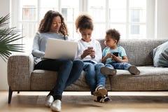 A família preta nova senta-se no sofá usando dispositivos fotos de stock