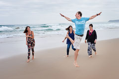 Família que é brincalhão junto na praia Fotos de Stock Royalty Free