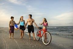 Família que anda abaixo da praia. imagens de stock