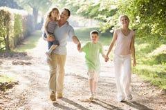 Família que anda ao ar livre prendendo as mãos e o sorriso Imagens de Stock