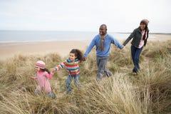 Família que anda ao longo das dunas na praia do inverno Fotos de Stock
