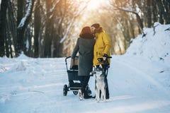 Família que anda com o carrinho de criança no inverno Foto de Stock Royalty Free