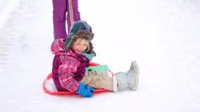 Família que anda em um parque do inverno Pais com a criança no trenó vídeos de arquivo