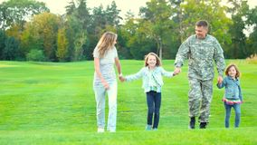 Família que anda na grama, guardando as mãos filme