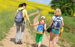 Família que anda na maneira ao campo do verão Imagem de Stock