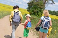 Família que anda na maneira ao campo do verão Foto de Stock