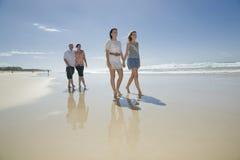 Família que anda nas mãos da terra arrendada da praia Imagens de Stock