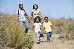 Família que anda nas mãos e no sorriso da terra arrendada do trajeto Imagens de Stock