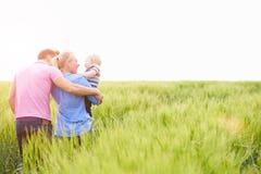 Família que anda no campo que leva o filho novo do bebê fotografia de stock