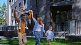 Família que anda no dia de verão no quintal da casa video estoque