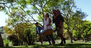 Família que anda no parque para o piquenique em um dia ensolarado 4k video estoque