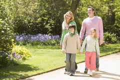 Família que anda no sorriso das mãos da terra arrendada do trajeto Imagens de Stock