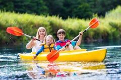Família que aprecia o passeio do caiaque em um rio Imagens de Stock