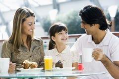Família que aprecia o petisco no café Imagens de Stock