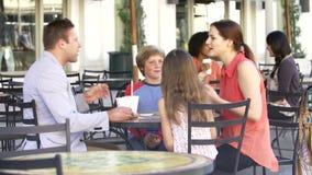 Família que aprecia o petisco no ½ exterior do ¿ de Cafï filme