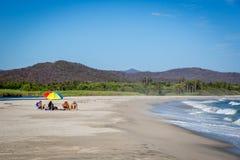 Família que aprecia os feriados em uma praia agradável da água azul em Baja California Imagens de Stock