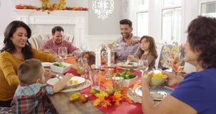 Família que aprecia a refeição da ação de graças na tabela disparada em R3D video estoque