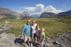 Família que caminha dentro nas montanhas bonitas do parque nacional de geleira Foto de Stock