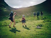 Família que caminha nas montanhas Uma mãe feliz nova e seu filho tomam uma caminhada junto nas montanhas em um bonito Fotografia de Stock Royalty Free