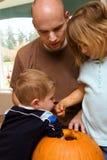 Família que cinzela a abóbora Foto de Stock Royalty Free