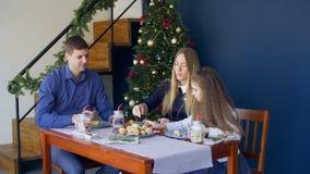 Família que come cookies do Natal na tabela festiva