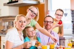 Família que come o café da manhã comum na cozinha Fotografia de Stock