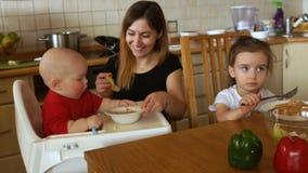 Família que come o café da manhã em uma cozinha ensolarada branca Mãe nova que alimenta duas crianças Nutrição saudável para cria filme