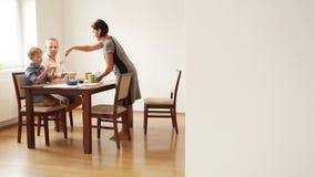 Família que come o café da manhã: a mãe põe a omeleta sobre suas placas do filho e do marido vídeos de arquivo
