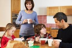 Família que come o pequeno almoço junto na cozinha Fotos de Stock