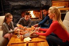 Família que come a pizza junto para o jantar fotografia de stock royalty free