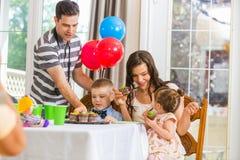 Família que come queques na festa de anos Foto de Stock Royalty Free