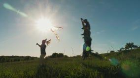 Família que corre com um papagaio em um prado em um dia ensolarado filme