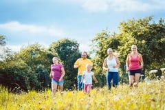 Família que corre em um prado para o esporte fotografia de stock