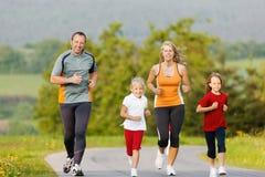 Família que corre para o esporte fora fotos de stock