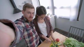 Família que cozinha, esposa feliz com a foto do selfie da tomada do marido no telefone ao cozinhar a refeição saudável dos vegeta video estoque
