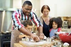 Família que cozinha o conceito da unidade do alimento da cozinha imagem de stock