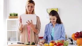 Família que cozinha o jantar usando o PC da tabuleta na cozinha video estoque