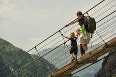 Família que cruza a ponte de suspensão Foto de Stock Royalty Free