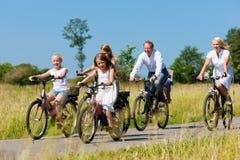 Família que dá um ciclo ao ar livre no verão Fotos de Stock Royalty Free