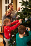 Família que decora a árvore de Natal em casa junto Foto de Stock
