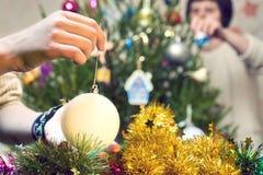 Família que decora uma árvore de Natal com as bolas do Natal no plano de Moscou fotos de stock