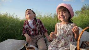 A família que descansa na natureza, crianças ri felizmente, bom humor, menina feliz e menino comendo a padaria, irmão e irmã que  vídeos de arquivo