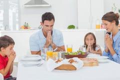 Família que diz a benevolência antes do jantar Fotos de Stock Royalty Free