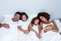 Família que dorme junto na cama imagem de stock royalty free